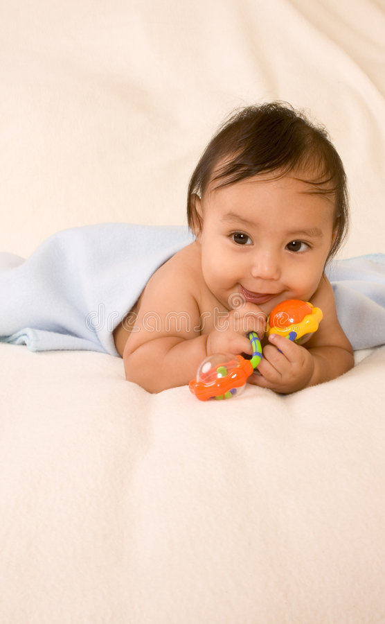 Ethnic baby boy with toy lying down on blanket royalty free stock photos