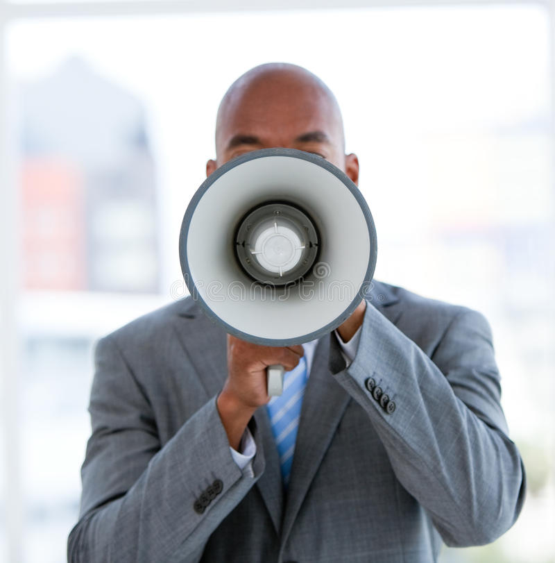 Ethnic businessman yelling through a megaphone. In the office royalty free stock photography