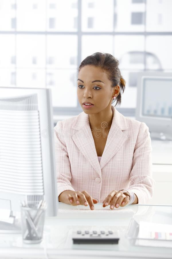 Ethnic businesswoman working at desk. Ethnic businesswoman sitting at desk working on desktop computer, looking at monitor, concentrating stock photo