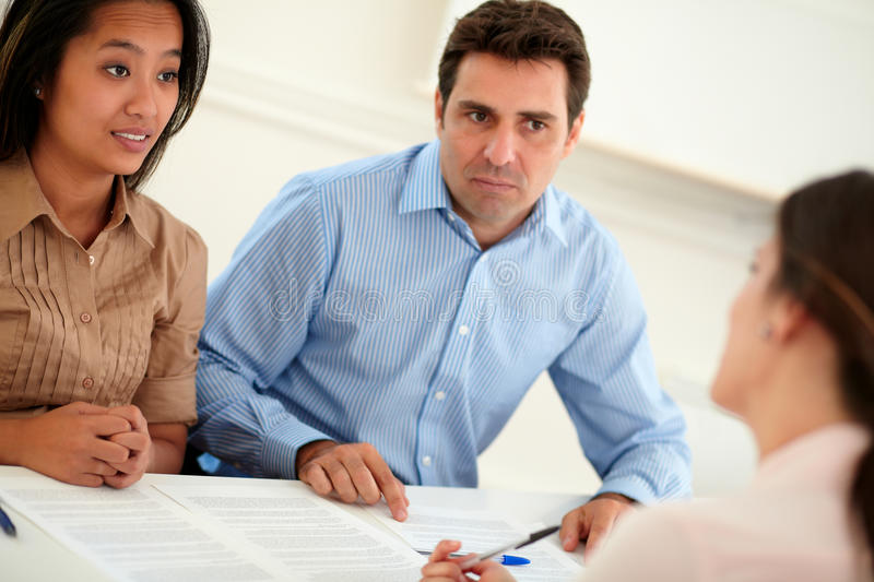 Ethnic couple interested in a contract. Portrait of ethnic couple interested in a contract sitting on office desk royalty free stock image