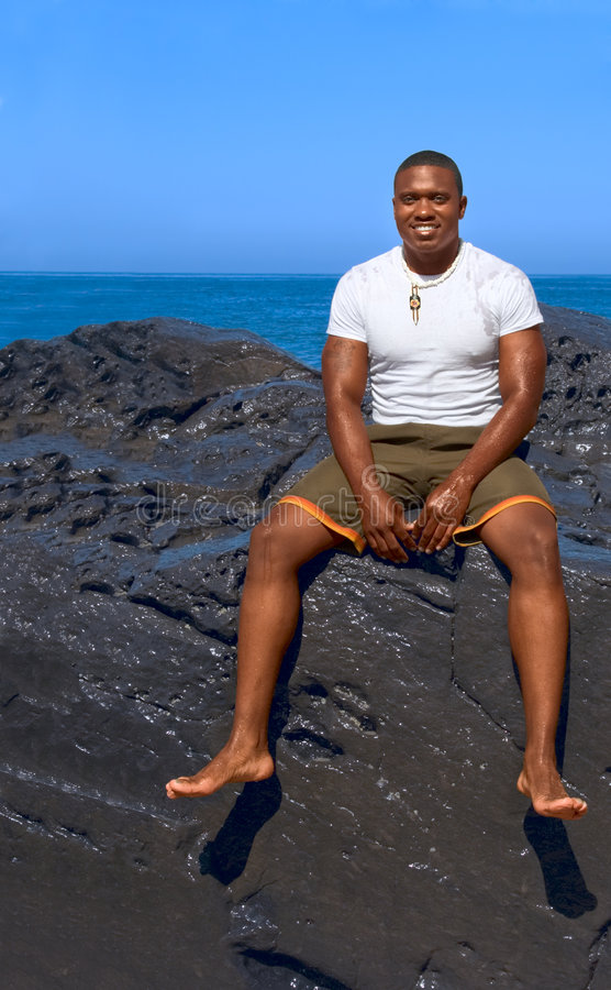 ethnic dark guy sitting on rock by sea beach royalty free stock image
