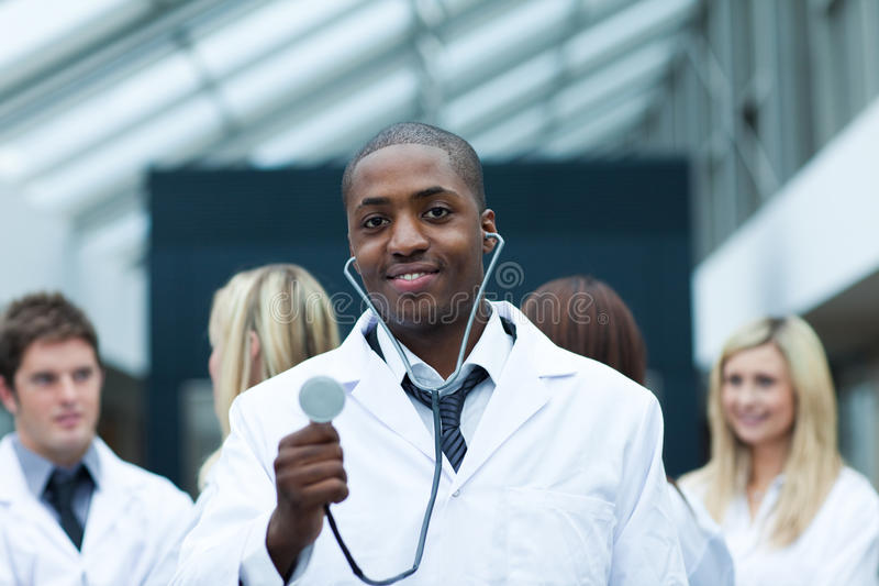 Download Ethnic Doctor With His Team In The Background Stock Photo - Image of cure, medicine: 10265604