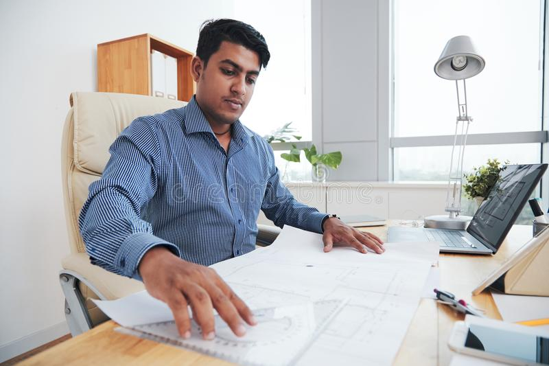 Ethnic engineer working in office stock image