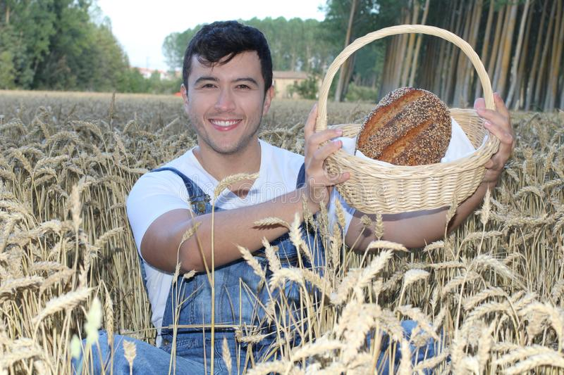 Ethnic farmer holding bread in wheat field stock photo