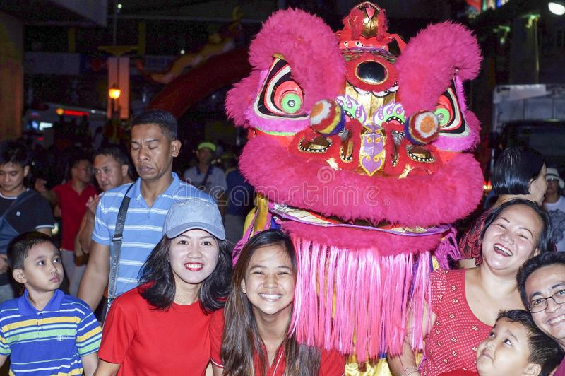 Ethnic Filipino Chinese Pose with Dancing Lion Mascot during New Year Celebration on the street royalty free stock photos