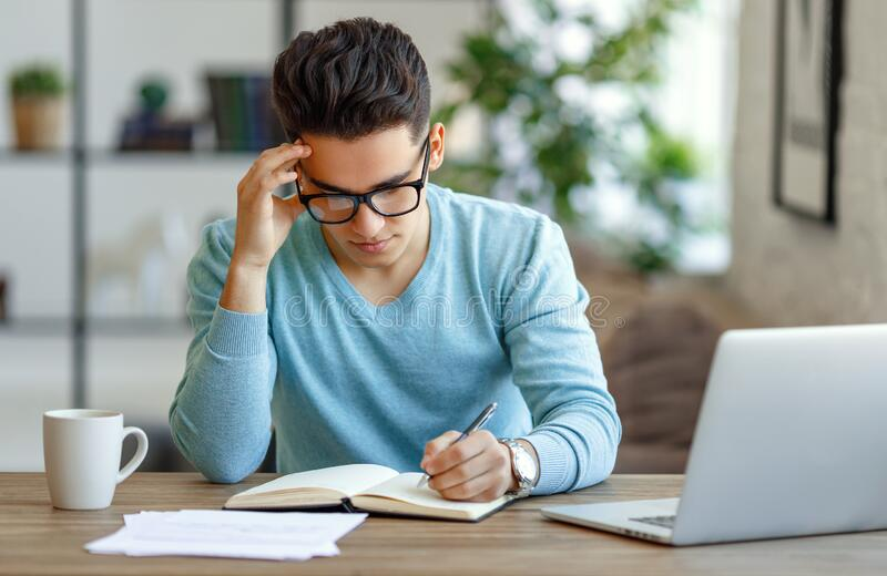 Ethnic freelancer making notes at home royalty free stock photos