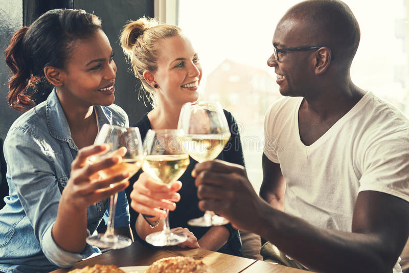 Ethnic friends at a bar. Drinking wine and eating tapas royalty free stock image