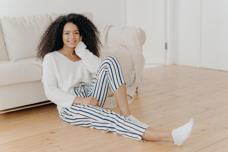 Ethnic girl feels relaxed and satisfied, sits on floor near comfortable sofa in empty room, wears white sweater, striped pants and stock photos