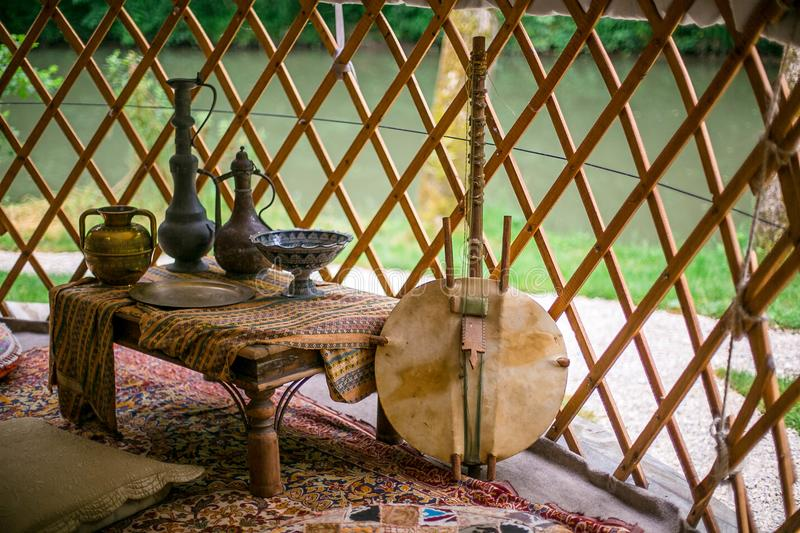 Ethnic hut decoration with dishes and national musical instrument royalty free stock photography