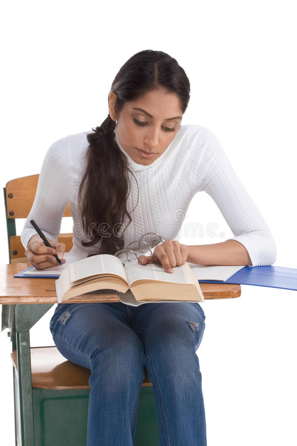 Ethnic Indian college student by desk in class stock images