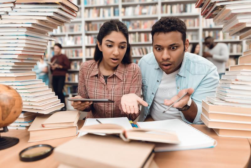 Ethnic indian mixed race girl and guy surrounded by books in library. Students are taking notes. royalty free stock photography