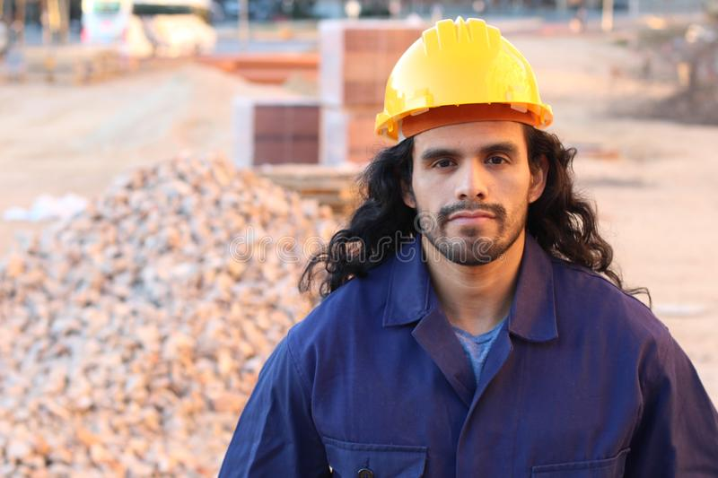 Ethnic long haired construction worker in site stock photography