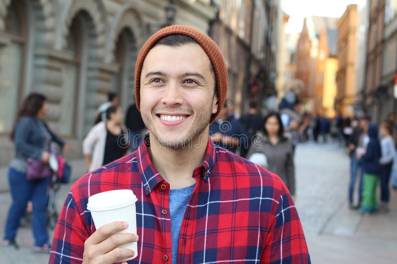 Ethnic male holding a disposable cup of coffee in the a crowded city street.  stock image