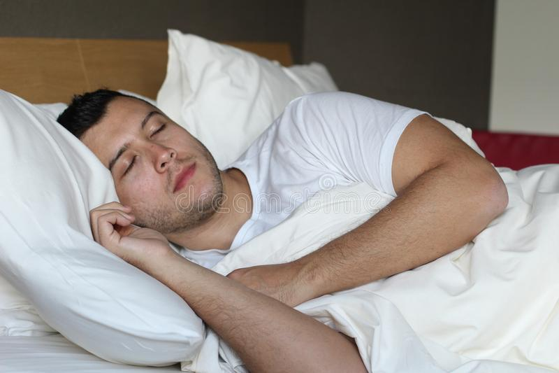 Ethnic man deeply slept in comfy bed.  stock image
