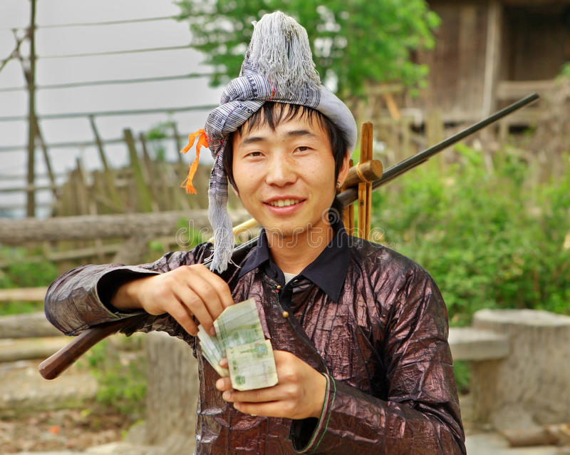 Ethnic Miao, Hmong Chinese. Guizhou Province, China. GUIZHOU PROVINCE; CHINA - APRIL 10: Man Miao ethnic group, with a musket on his shoulder, counts Yuan stock photo