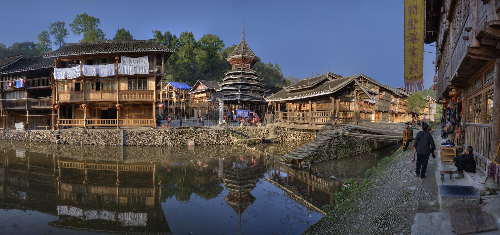 Ethnic minorities village, wooden house reflected water, Zhaoxing, Guizhou, China. Zhaoxing Village, Guizhou Province, China - April 8, 2010: Spring sunny royalty free stock image