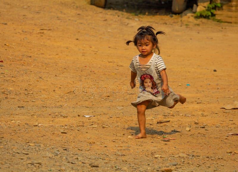 Ethnic minority child walking in a village Laos stock photos