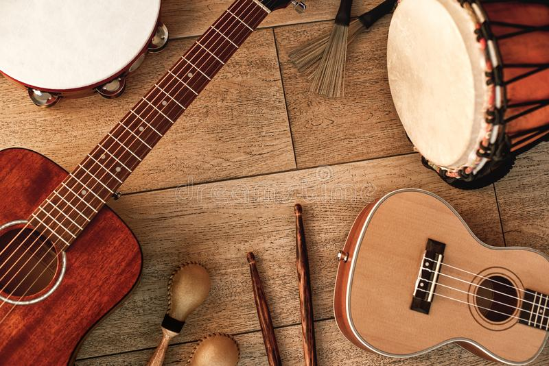 Ethnic musical instruments set: tambourine, wooden drum, brushes, wooden sticks, maracas and guitars laying on wooden stock photos