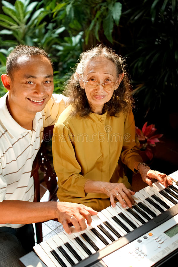 Download Ethnic Old Mother And Son Happy Playing Piano Stock Image - Image: 23810501