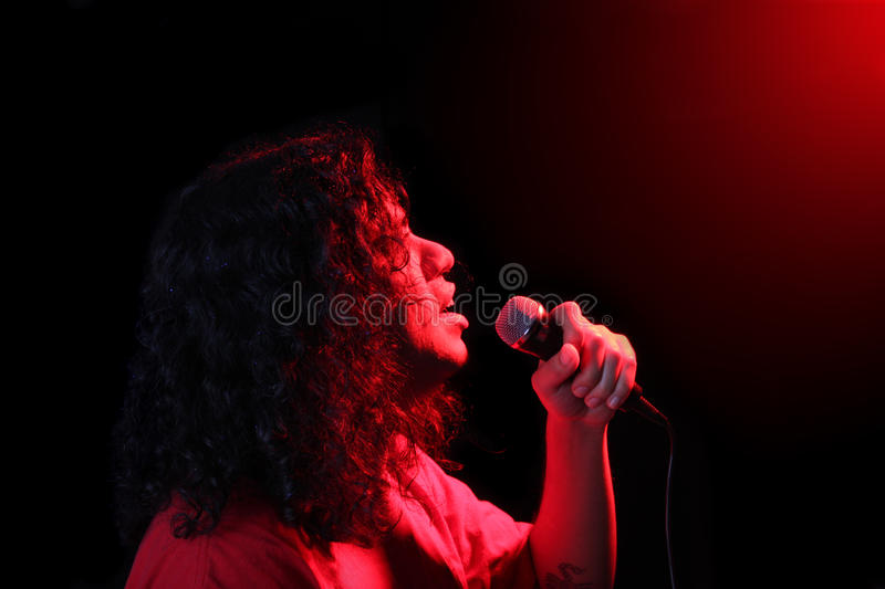 Ethnic singer. Ethnic male singer in with red concert spotlights shining stock photo