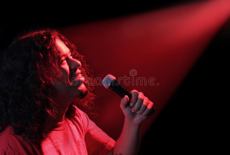 Ethnic singer. Ethnic male singer in with bright red concert spotlights shining royalty free stock photography