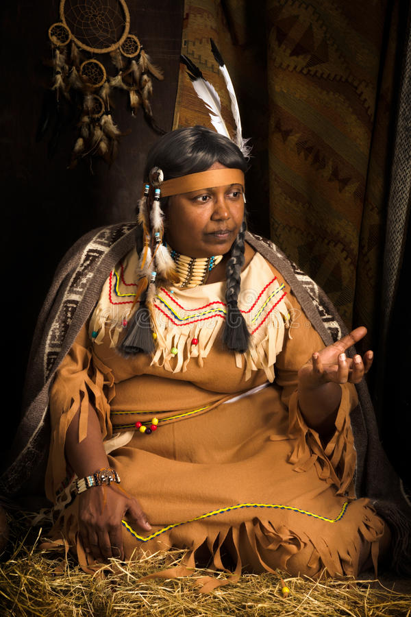 Ethnic stories. Weathered mature tribal female storyteller talking about heroic times stock photo