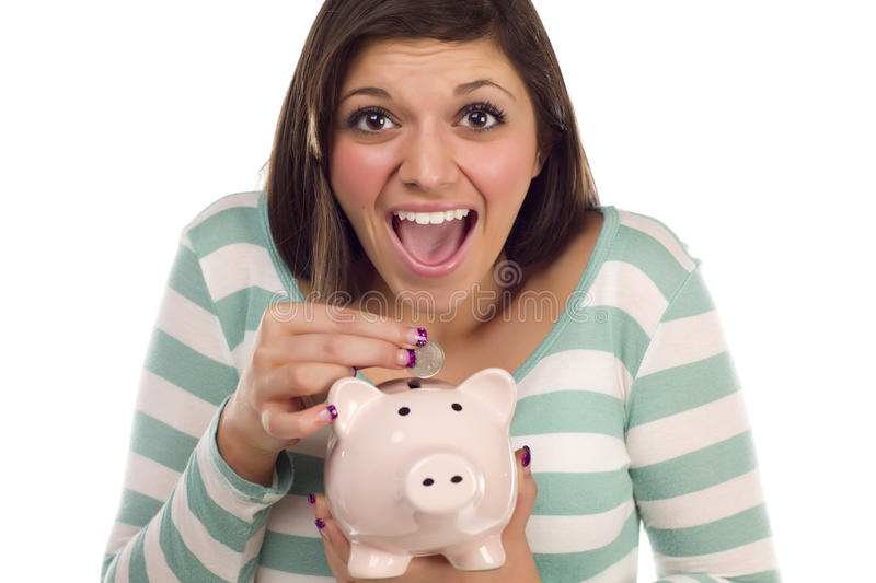 Ethnic Teen Putting Coin Into Piggy Bank on White. Pretty Smiling Ethnic Female Putting a Coin Into Her Pink Piggy Bank Isolated on a White Background stock images