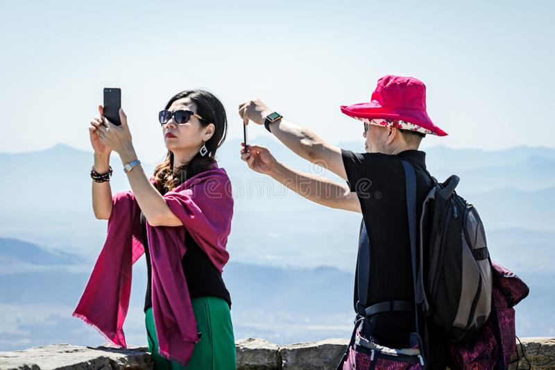 Ethnic tourists taking photos with phone technology. Cape Town, South Africa, 2nd October 2017 Ethnic male and female tourists taking photos with phone cameras royalty free stock images