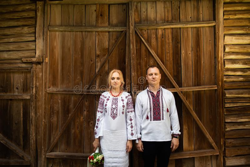 Ethnic wedding in national costumes. Ukrainian marriage bride and groom standing on the background of a wooden wall royalty free stock images