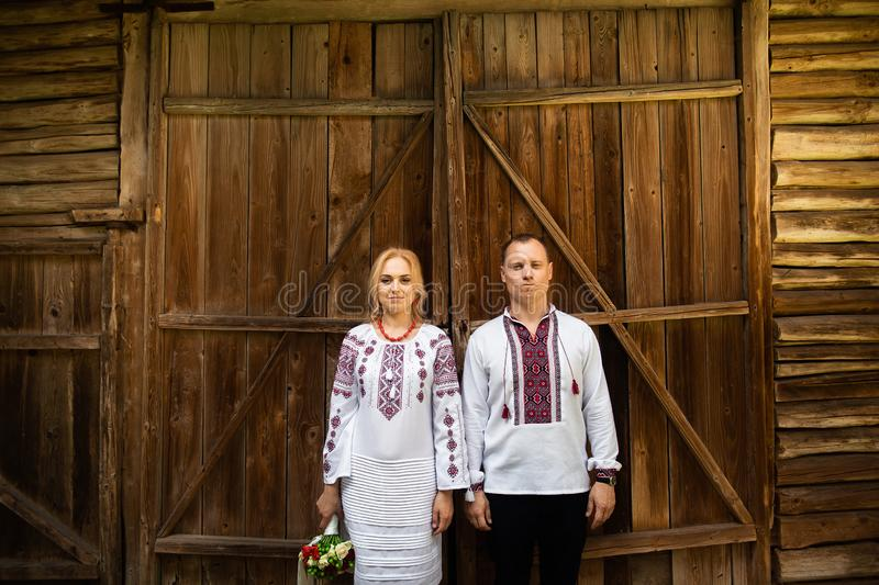 Ethnic wedding in national costumes. Ukrainian marriage bride and groom standing on the background of a wooden wall royalty free stock photo