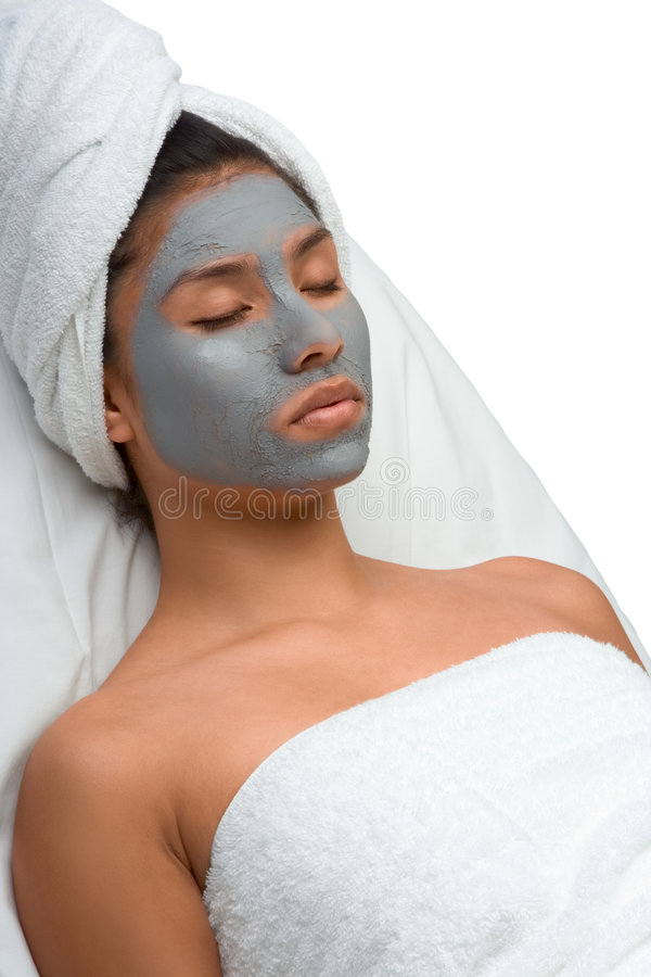 Ethnic woman relaxing during facial in spa stock images