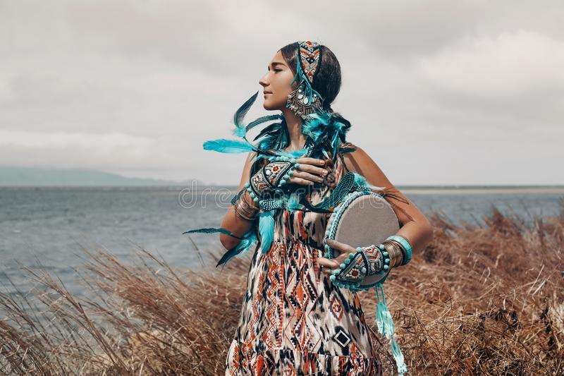 Attractive young woman in ethnical costume on a field at sea royalty free stock images