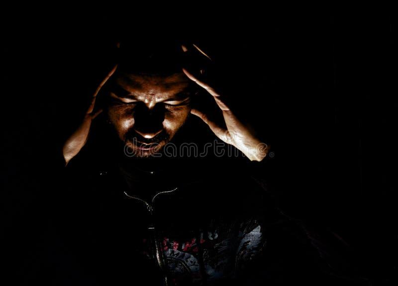 Ethnisch gemischter Mann in der dunklen Kleidung mit Kopfschmerzen vom Druck stockfotografie