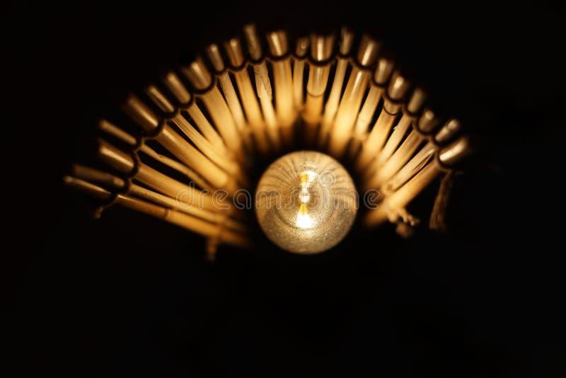 Ethnische Bambuslampe, scheint wie Auge Mann, der Energiesparende Gl?hlampen jongliert stockfoto