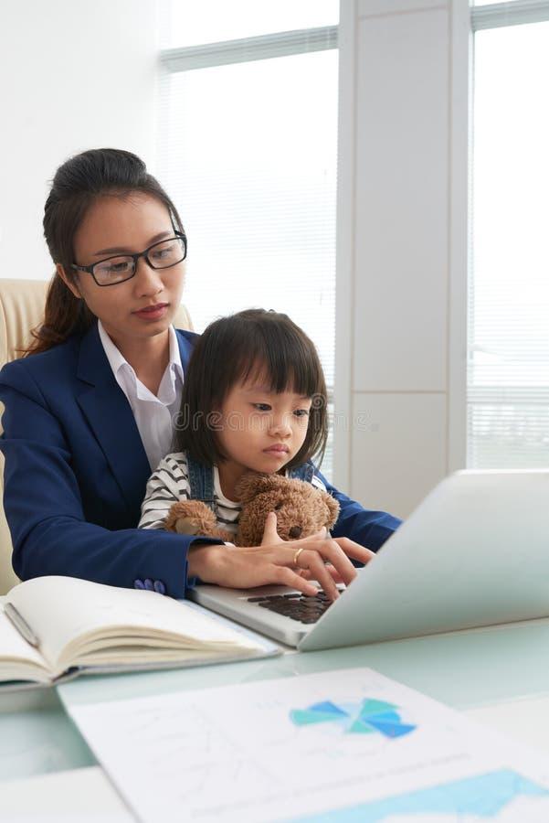 Ethnische Geschäftsfrau mit Kind bei der Arbeit lizenzfreie stockbilder