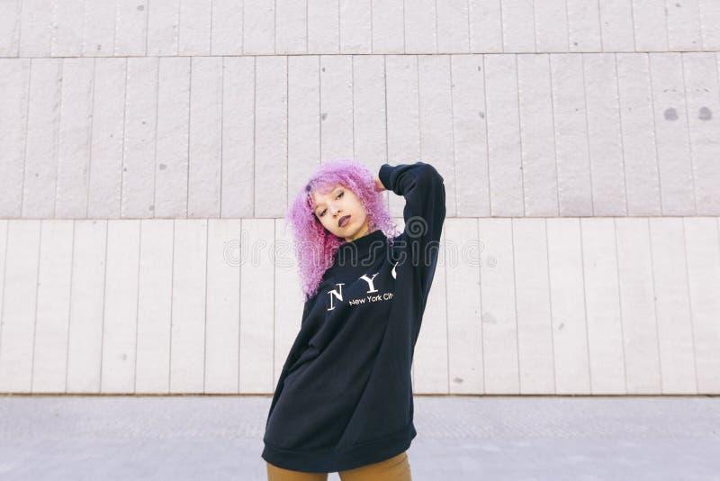 Ethnische schwarze junge Frau mit dem rosa Haar und einer New- Yorkstrickjacke stockbild