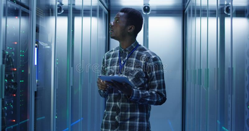 Ethnischer IT-Fachmann mit Tablette im Serverraum lizenzfreie stockfotografie