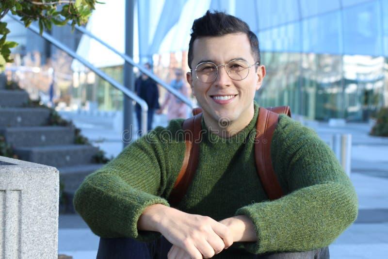Ethnischer Studentenmann, der auf dem Campus lächelt stockfoto