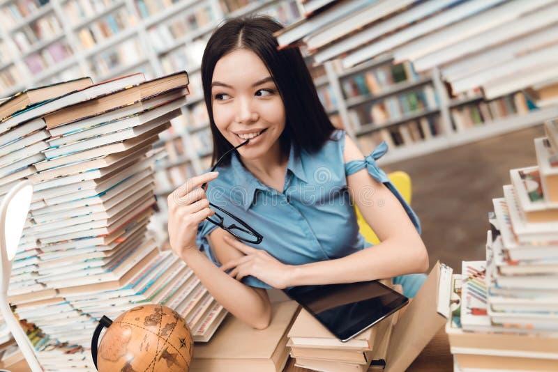 Ethnisches asiatisches Mädchen umgeben durch Bücher in der Bibliothek Student benutzt Tablette lizenzfreie stockfotografie