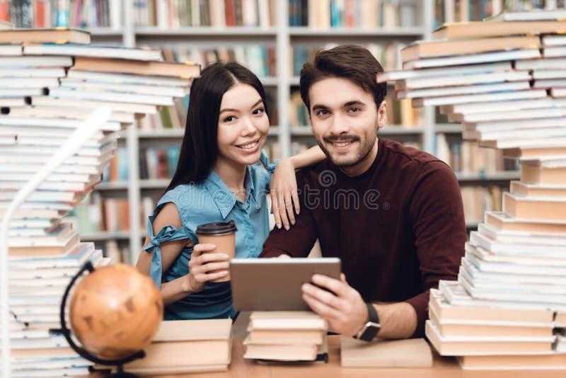 Ethnisches asiatisches Mädchen und weißer Kerl umgeben durch Bücher in der Bibliothek Studenten benutzen Tablette stockfotos