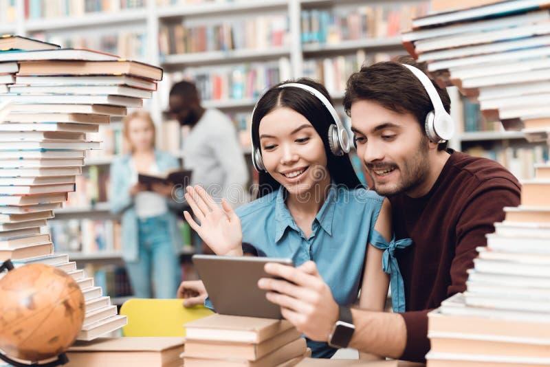 Ethnisches asiatisches Mädchen und weißer Kerl umgeben durch Bücher in der Bibliothek Studenten benutzen Tablette mit Kopfhörern lizenzfreies stockfoto
