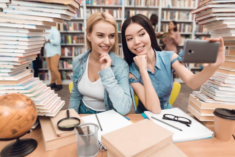 Ethnisches asiatisches Mädchen und weißes Mädchen umgeben durch Bücher in der Bibliothek Studenten nehmen selfie lizenzfreies stockfoto