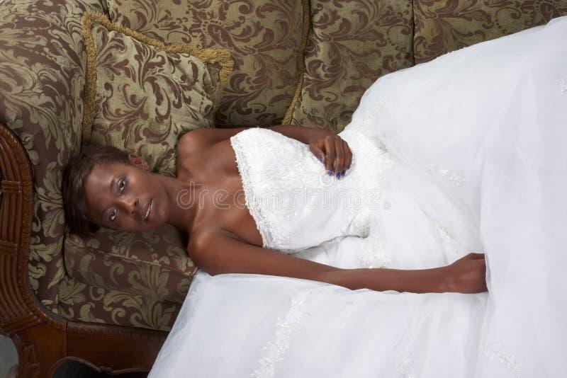 Ethnisches Braut-Hochzeitskleid der schwarzen Frau auf Couch lizenzfreies stockfoto