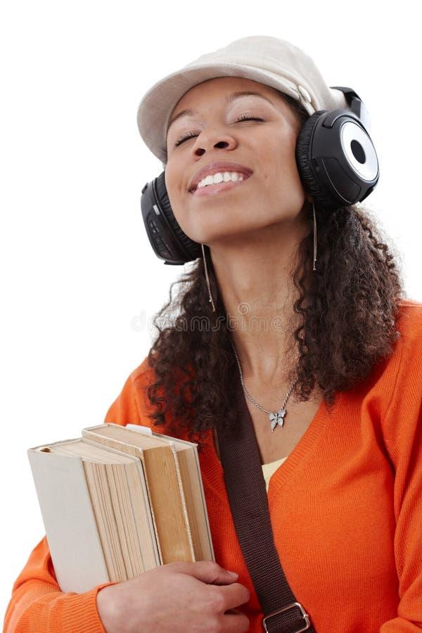 Ethnisches Mädchen, das Musik durch Kopfhörer genießt stockfotografie