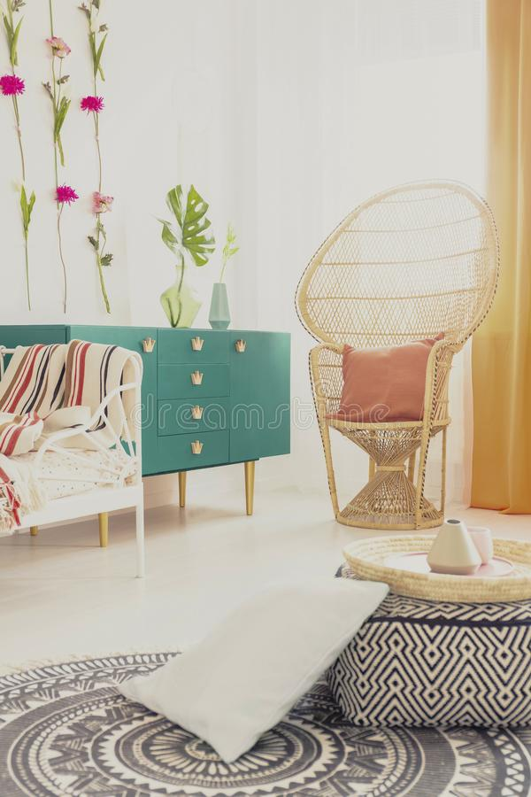 Ethnotapijt op witte vloer van modieus slaapkamerbinnenland met groen meubilair en rieten pauwstoel royalty-vrije stock fotografie