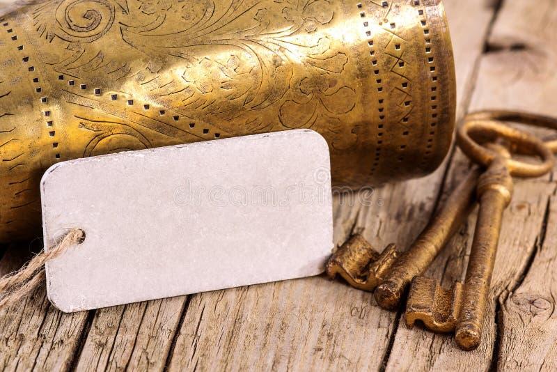 Etichetta in bianco con la vecchia tazza dorata e le chiavi immagini stock
