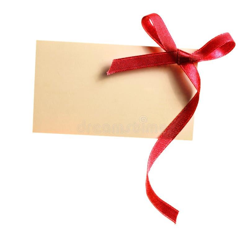 Etichetta in bianco del regalo legata con un arco del nastro rosso del raso. Isolato su bianco immagine stock