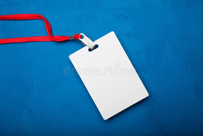 Etichetta in bianco vuota della carta di identità isolata su fondo blu Modello immagini stock