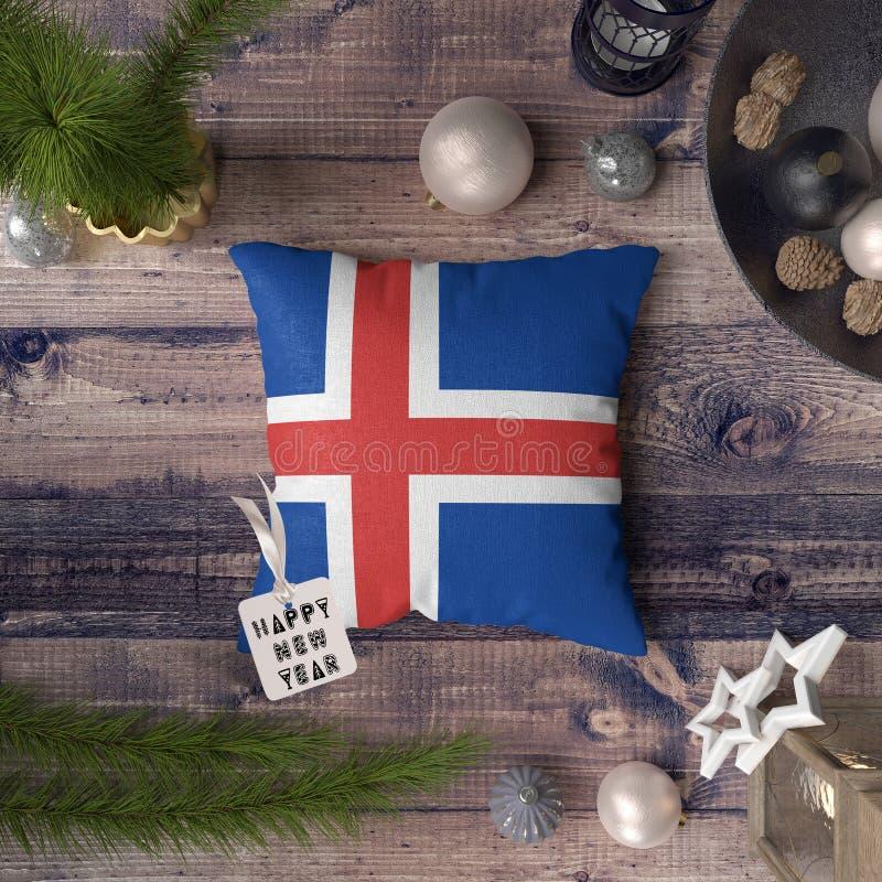 Etichetta del buon anno con la bandiera dell'Islanda sul cuscino Concetto della decorazione di Natale sulla tavola di legno con g fotografia stock libera da diritti