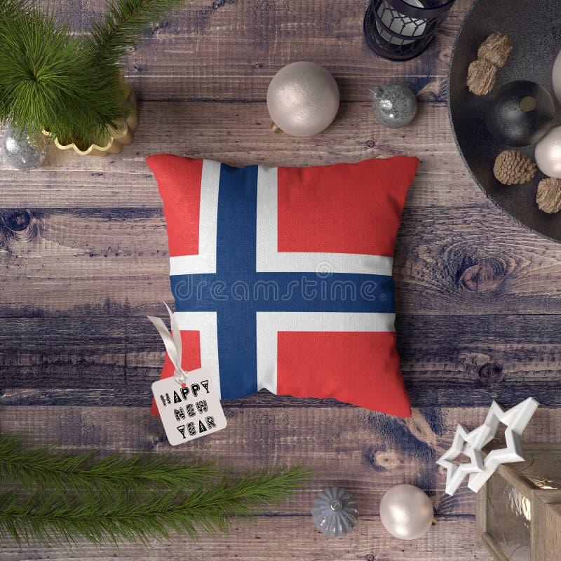 Etichetta del buon anno con la bandiera della Norvegia sul cuscino Concetto della decorazione di Natale sulla tavola di legno con fotografia stock libera da diritti